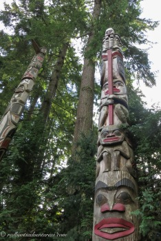 Two totem poles and tall trees