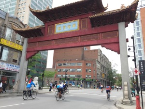 Cyclists riding through red gate Montreal's Chinatown