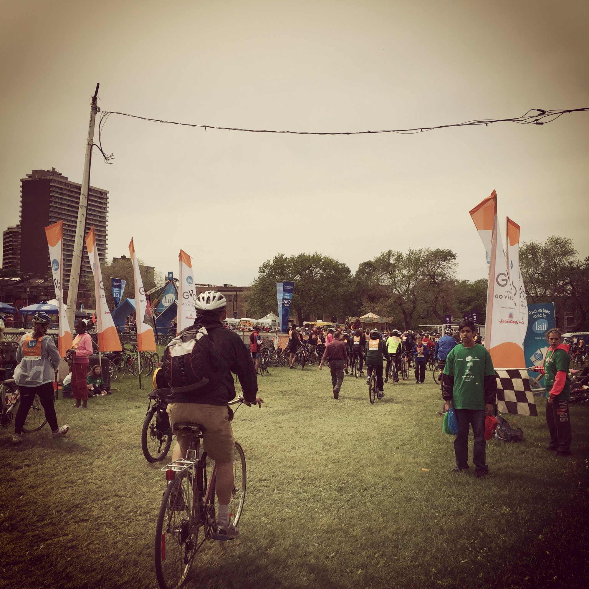 Cyclist riding through orange flags at the finish line