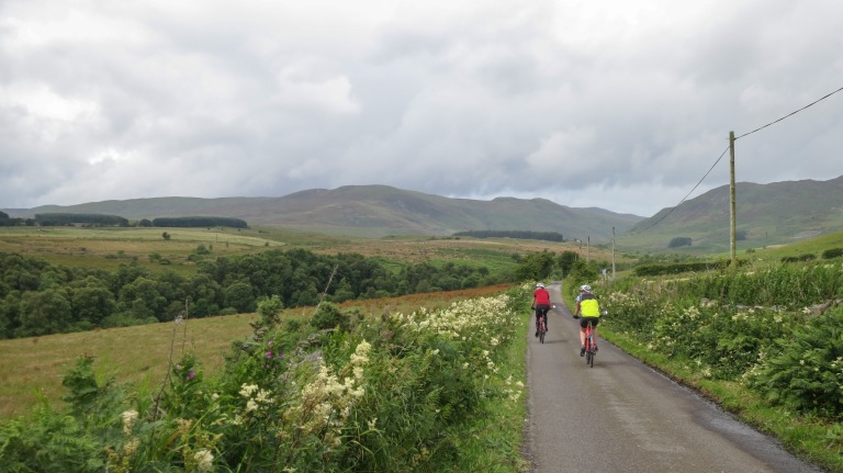 Two cyclist on the road to Scottish highlands
