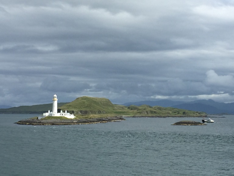 white lighthouse and fishing boat scotland